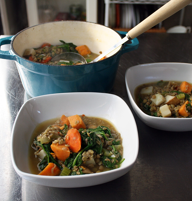 a bowl of lentil stew with spinach and potatoes
