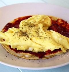 a grilled cheese made with corn tortillas, slathered with harissa and topped with scrambled eggs